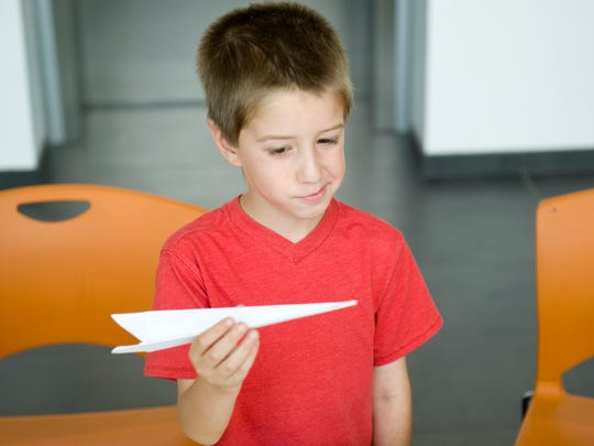 DENNY SIMMONS / COURIER & PRESS Matthew Payne, 6, of Evansville gives his newly created paper airplane the once-over before taking it into the flight room at the Evansville Museum during Paper Airplane Day. The museum is hosting another paper airplane contest Saturday.