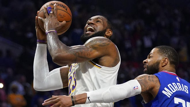 Los Angeles Lakers forward LeBron James, left, shoots as Los Angeles Clippers forward Marcus Morris Sr. defends during the second half of a game in March.