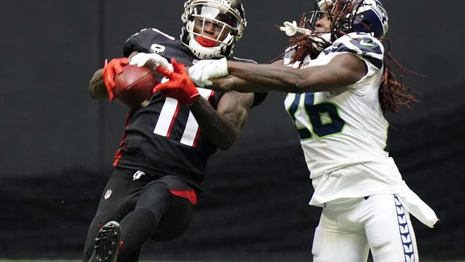 Atlanta Falcons wide receiver Julio Jones (11) makes the catch aganst Seattle Seahawks cornerback Shaquill Griffin (26) during the second half of an NFL football game, Sunday, Sept. 13, 2020, in Atlanta.