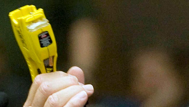 A Calif. district attorney shows a Taser during a hearing. AP file.