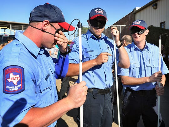Wichita Falls Fire Department recruits Brenton Sullivan, left, Craig Kerr and Lance Raub don their blindfolds and canes before heading out for White Cane Day at the Beacon Lighthouse Wednesday.