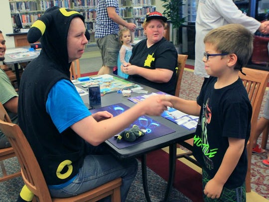 Ray Bryan (left), of Pickens, dressed as a Pokemon character, shakes hands with Luke Taylor (right) of Belton, who beat the elder in a Pokemon card game at Electric City ComiCon at the Anderson County Library in Anderson.