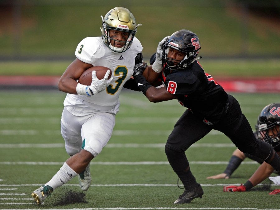 wade payne/special to the news sentinel Catholic's Amari Rodgers stiff arms Central's Edward Brodie on Friday at Central High School.