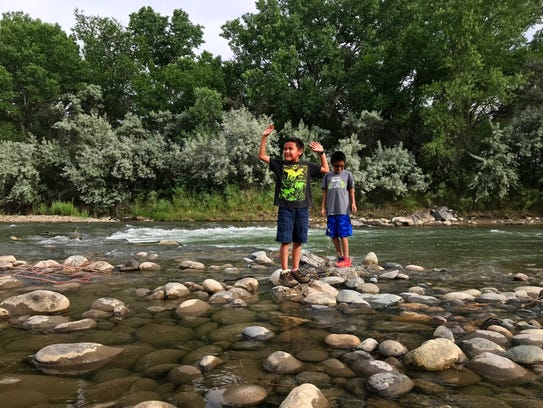 Thomas Dale, left, and Drake Dale, both from Shiprock, take a break from their walk to play in the Animas River Wednesday during the Just Move It event at Berg Park in Farmington.