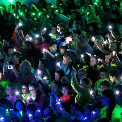 Students shine lights simulating fireflies as they