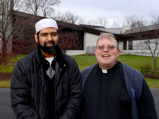 "Rev. Fred Fritz, right, of University Lutheran Church and Imam Sohail Chaudhry of the Islamic Center of East Lansing, stand together in the ""bridge"" area between their two buildings Thursday, December 10, 2015. The two religious communities have built a friendship that includes sharing parking spaces, green space, landscaping and more."