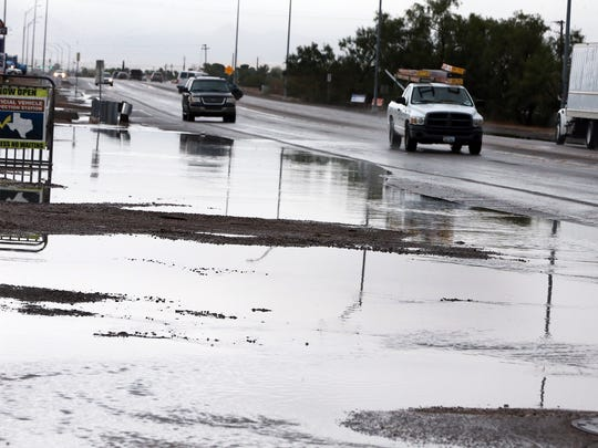 Traffic flows by standing water along Doniphan Drive from morning rains in September.