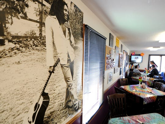 Bob Marley looks over dining room tables covered in tie-dyed cloths at Tie Dye Grill  at Tie Dye Grill on Indianapolis' east side, 1311 N. Shadeland Ave.