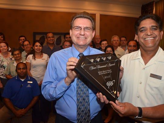 AAA Motor Club Manager Doug Harper, left, presents
