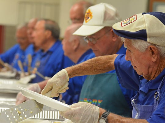 Bill Lewis, right, dishes up the chow with his fellow volunteers. San Marco Catholic Church's Knights of Columbus packed in the diners for their Friday fish fry at the parish hall in 2014.