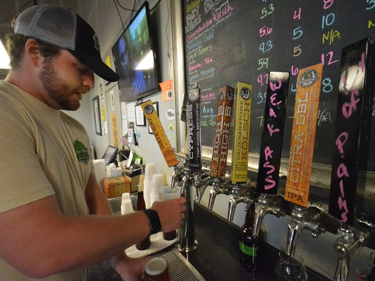 "Bartender Cody Lewis pours ""Gateway Gold,"" a top-selling pale ale at Fort Myers Brewing Company."