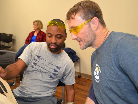 DeJuan Surrell of Jackson, left, and Joey Brinson of Florence, right, look at how close Surrell got to the bullseye during target practice at Two Gun Tactical in Flowood. Both participated in a marksmanship clinic organized by Ginny Boydston, director of the adaptive sports and recreation program at Methodist Rehabilitation Center in Jackson.