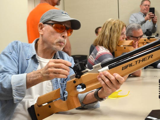 John Berret of Madison, left, and Michelle Cox of Edwards, right, take aim during a marksmanship clinic at Two Gun Tactical in Flowood. Methodist Rehabilitation Center in Jackson organized the clinic to introduce marksmanship, a Paralympic competition, to Mississippians with physical disabilities.