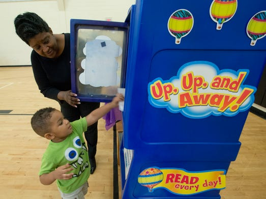 Three-year-old Tyson Stevenson puts the first book into the children's Little Free Library with help from his Great-Grandmother Linda Gulley at the Marie K. Young Wedgewood Community Center Friday morning Aug. 8, 2014.