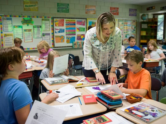 Angie Wright helps student Andy Fisher with instructions during a social studies lesson about Marco Polo in her Fifth grade class at Sharon Elementary School in Newburgh.