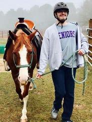 A participant walks beside a horse at Purposeful Refuge