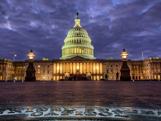 Lights shine inside the U.S. Capitol Building as night