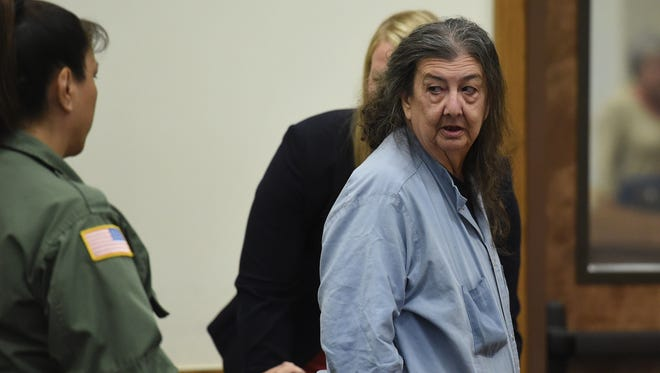 Cathy Woods, right, who had been imprisoned for more than 30 years, looks toward a deputy sheriff in a Washoe district court in Reno on Sept. 8, 2014.
