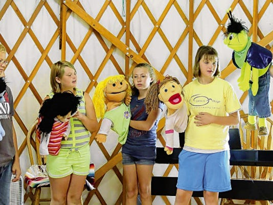 Campers from 2014 participate in a puppet show at the Peace Village Day Camp.