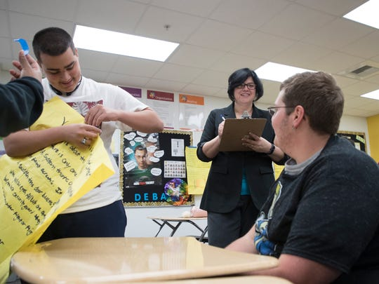 Milagros Sowers, a debate teacher at East Lee County High School goes over an assignment with her students during class recently. Sowers was named a 2017 Golden Apple recipient.