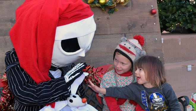 Aizel Luther (Left) Age 9 and Dinah K. (Right) Age 3 have fun talking to Jack Skellington at this years Christmas Craft Fair held at the Plaza de Las Cruces on Saturday Morning.
