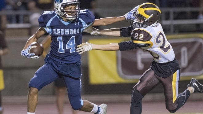 Redwood's La'Dre Aguilar keeps Golden West's Zachary Hart away in a West Yosemite League high school football game on Friday, September 29, 2017.