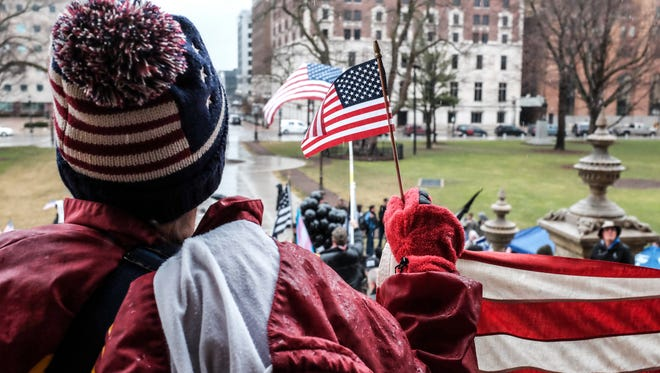 American flags are waving at the Michigan Make America Great Again March at the State Capitol Saturday, March 25, 2017. About 100 people attended the event with about half of them protesting the event.