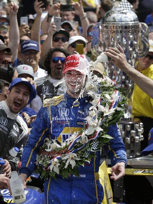 Indy 500 winner Alexander Rossi has the customary victor's milk poured on him.
