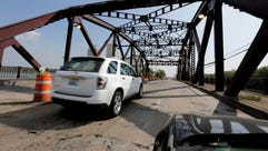 Cars drive on the 130th St. bridge over the Little