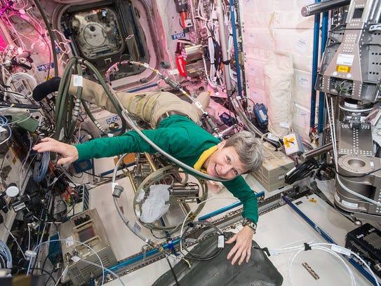 NASA astronaut Peggy Whitson floats through a tangle