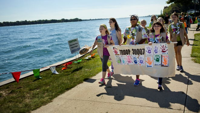 Girl Scouts from Troop 30007 carry a banner in a parade along the St. Clair River during the 2014 Girl Scouts International River Crossing at Nautical Mile Park in Marine City.