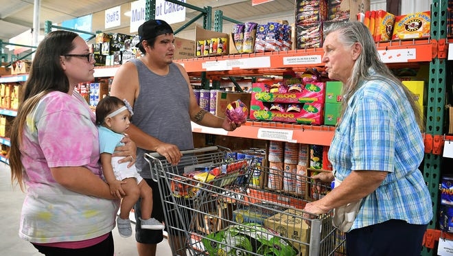 Patsy Hodgkins, owner of Russell's Fireworks, answers questions for Jerrod Haag, his wife, Rani and daughter, Blayke, as they shop for fireworks Tuesday afternoon.