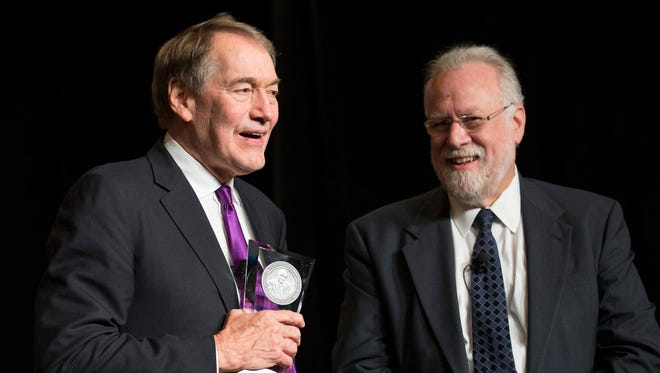 Charlie Rose (left) smiles after receiving an award from ASU Provost Dr. Mark Searle in 2015.