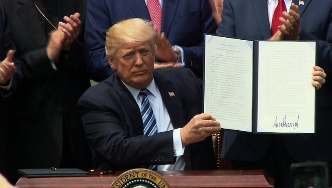 "President Donald Trump signs an executive order to 'vigorously promote religious liberty."""