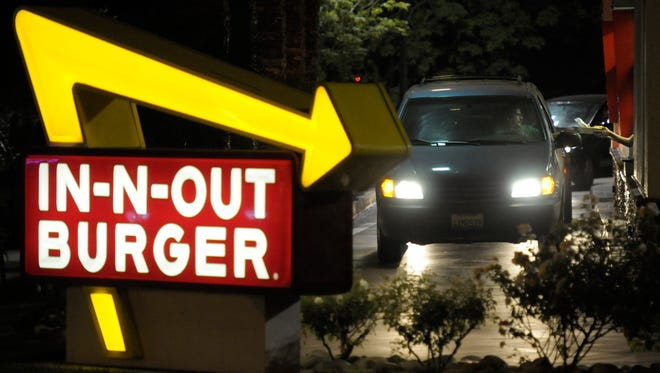 In this June 8, 2010 photo, a customer receives an order from the drive-through at In-N-Out Burger in Baldwin Park, Calif. Amid complaints of obesity and lines of idled cars stretching into neighborhood streets, this blue-collar town is banning new drive-throughs in hopes of shedding its reputation as a haven for convenient, fatty foods. (AP Photo/Adam Lau)
