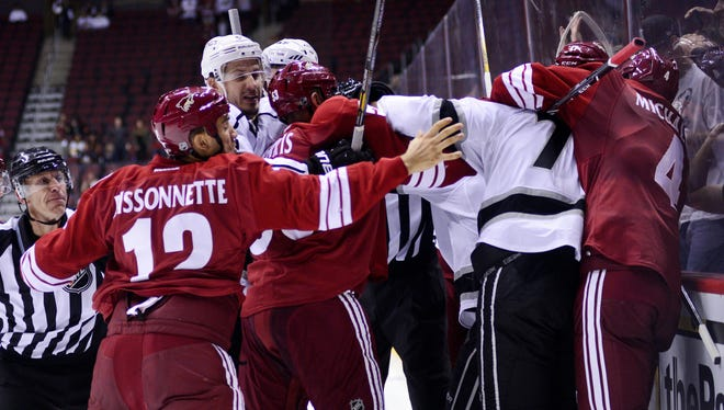 Phoenix Coyotes winger Paul Bissonnette (12) gets involved in a scrum after Jordan Nolan, who earlier hit Rostislav Klesla. The league says he jumped off the bench and suspended him for 10 games.
