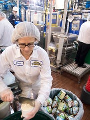 Brenda Noyes examines some fresh Coffee Toffee Bar Crunch that just came off Line 1 as a team at Ben & Jerry's factory in St. Albans readies for a run of the flavor that now sources non-GMO ingredients.