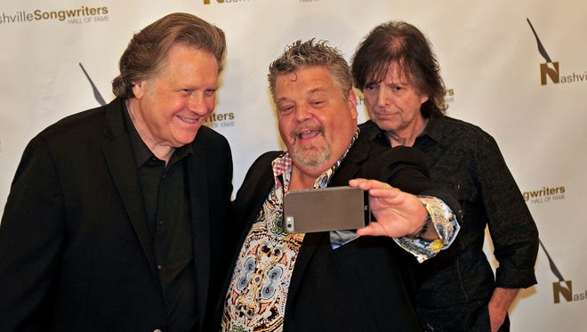 Nashville Songwriters Hall of Fame Foundation inductees Craig Wiseman, center, takes a selfie with Mark James, left, and Even Stevens after a news conference in Nashville, Tenn. The three, along with Rosanne Cash, will be inducted tonight.
