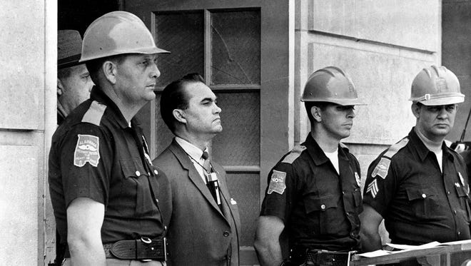 Gov. George Wallace blocks the entrance to the University of Alabama as he turned back a federal officer attempting to enroll two black students at the university campus in Tuscaloosa, Ala., June 11, 1963.  The 43-year-old governor stands with highway patrolmen who are on duty to prevent violence.  (AP Photo)