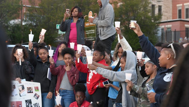 Members of My Sistah Taught Me That and My Daddy Taught Me That hold candles candles during a vigil for Harmony Smith, 13, and Keithan Whitmire, 15, on Thursday, April 19, 2018. Harmony, who was part of the organization, her brother, Keithan, and mother were shot and killed by her mother's boyfriend in West Asheville on Wednesday night.