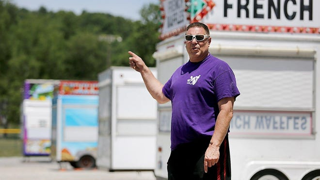 Brad Palmer, president of the Minerva Community Association, points out where more food vendors will be set up for the three-day Fair Food in the Park.