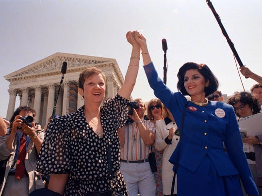 Norma McCorvey (left), Jane Roe in the 1973 court case, and her attorney Gloria Allred hold hands as they leave the Supreme Court on April 26, 1989 in Washington, DC., after sitting in while the court listened to arguments in a Missouri abortion case.