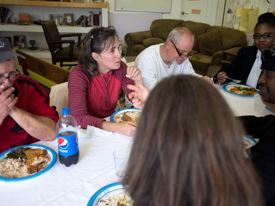 The Rev. Shannon Spencer shares a meal with friends and other community organizers Thursday April 5, 2016 at 12 Baskets cafe in West Asheville.