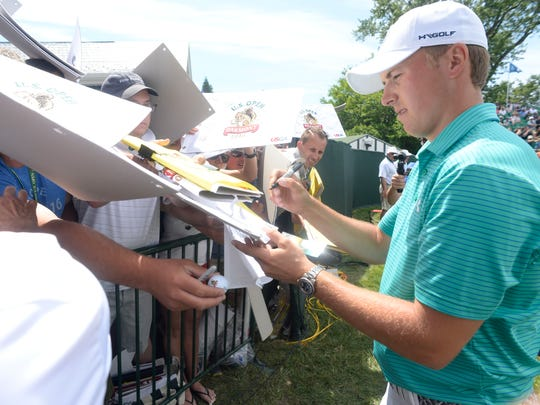 Jordan Spieth signs autographs on the 18th green during