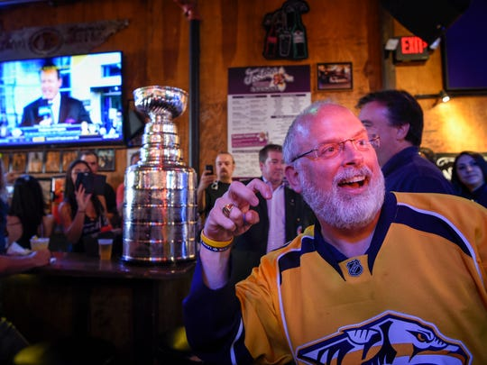 Nashville Predator fan Eddie Johnston gestures as he gets his picture made in front of the Stanley Cup as it visits Tootsie's Orchid Lounge in Nashville, Tenn., Wednesday, May 31, 2017.