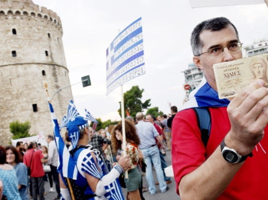 A supporter of the NO vote in the upcoming referendum, holds an old 1,000 drachma bank note during a rally Monday in the northern Greek port city of Thessaloniki.