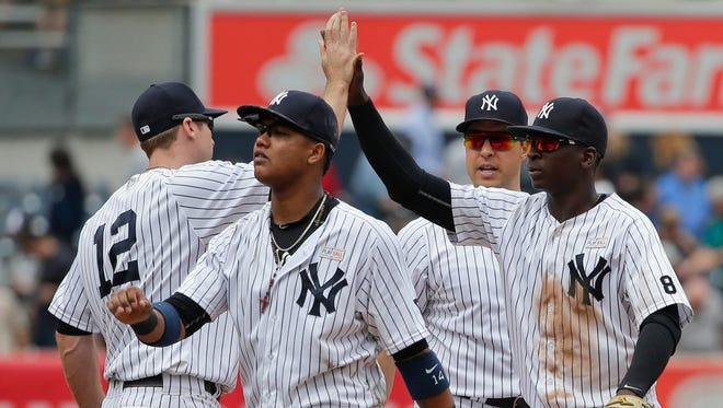 New York Yankees' Chase Headley, left, and Starlin Castro, second from left, celebrate with teammates Mark Teixeira, and Didi Gregorius, right, after a baseball game against the Chicago White Sox Saturday, May 14, 2016, in New York. The Yankees won 2-1. (AP Photo/Frank Franklin II)