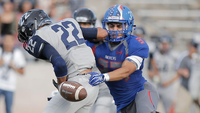 Americas' Elijah Escamilla separates Del Valle's Raymond Morales from the football during their season opener Thursday at the Socorro Student Activities Complex.