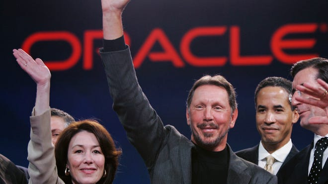 Larry Ellison, center, smiles with now-Oracle  co-CEO Safra Catz, left, during the Oracle Open World conference Oct. 25, 2006, in San Francisco.