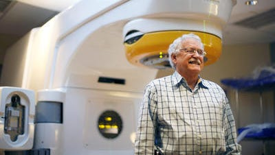 Gene King sits in front of the Novalis TX machine TMH Cancer Center where he received treatment for trigeminal neuralgia, a chronic pain condition that affects the trigeminal nerve, which carries sensation from your face to your brain.